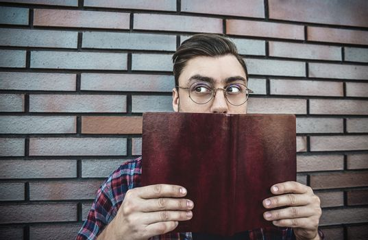 Portrait of smiling handsome man in round glasses and shirt isolated on brown brick wall.