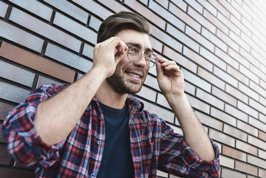 Portrait of smiling handsome man in round glasses and shirt isolated on brown brick wall