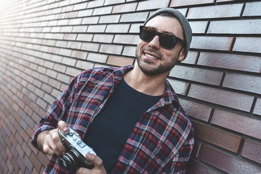 Smiling man with sunglasses hold retro photo camera Fashion Travel Lifestyle outdoor while standing against brick wall background.