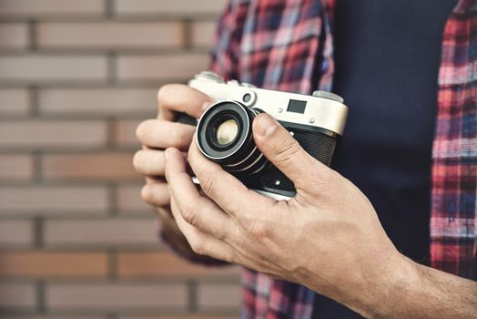 Close up photo man with retro photo camera Fashion Travel Lifestyle outdoor while standing against brick wall background.