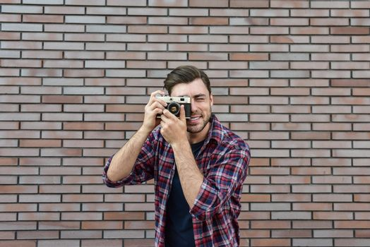 Man with retro photo camera Fashion Travel Lifestyle outdoor while standing against brick wall background.