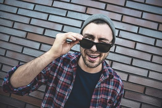 Young adult man wearing sunglasses standing over brown brick wall smiling with happy face winking at the camera.