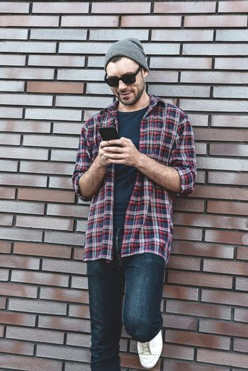 Hipster sms texting phone app in city street on brick wall background. Amazing man holding smartphone in smart casual wear standing. Urban young professional lifestyle.