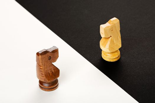 wooden chess knights on black and white background, abstract concept