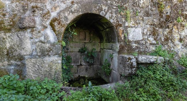 old stone water source in portugal - ancient well in the countryside