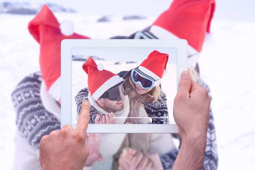 Hand holding tablet pc against close up of a cheerful couple in ski goggles on snow