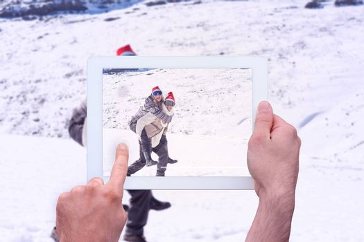 Hand holding tablet pc against full length of a man piggybacking cheerful woman on snow