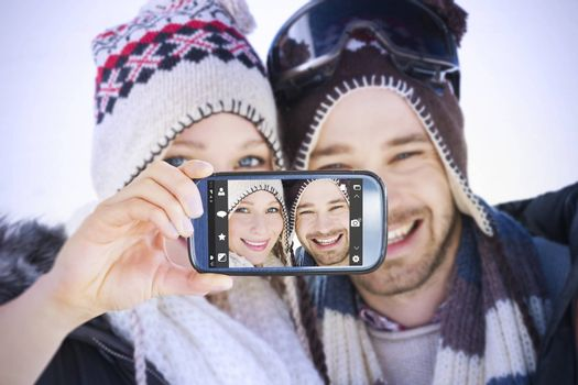 Hand holding smartphone showing against close up portrait of a smiling couple in woolen hats