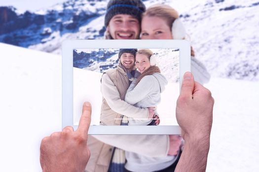Hand holding tablet pc against loving couple in warm clothing on snowed landscape