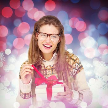 Happy geeky hipster smiling at camera and holding present against snowflake pattern
