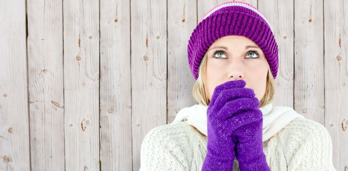 Composite image of freezing young woman wearing gloves looking upwards