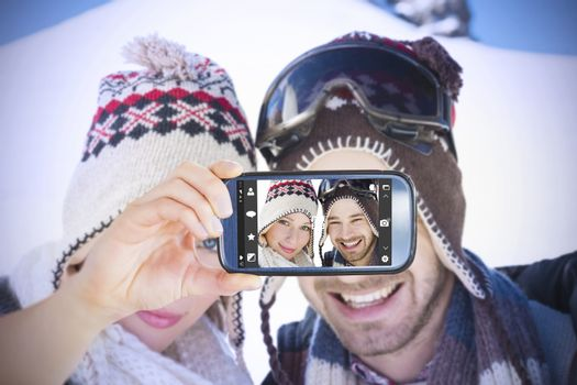 Hand holding smartphone showing against smiling couple in woolen hats on snow covered landscape