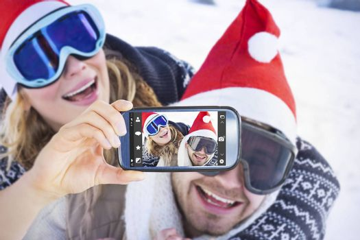 Hand holding smartphone showing against close up of a cheerful couple in ski goggles on snow