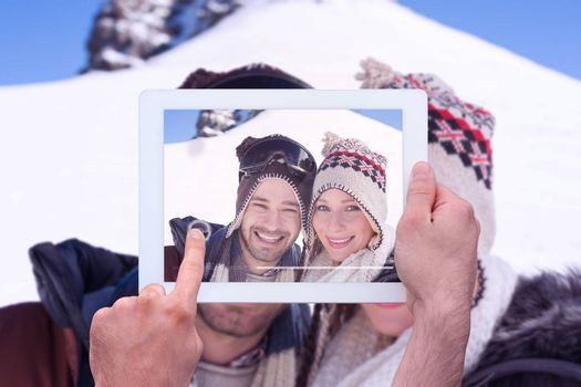 Hand holding tablet pc against close up portrait of a smiling couple in woolen hats
