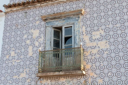 broken window of a typical ruined house with its tiled facade in Portugal