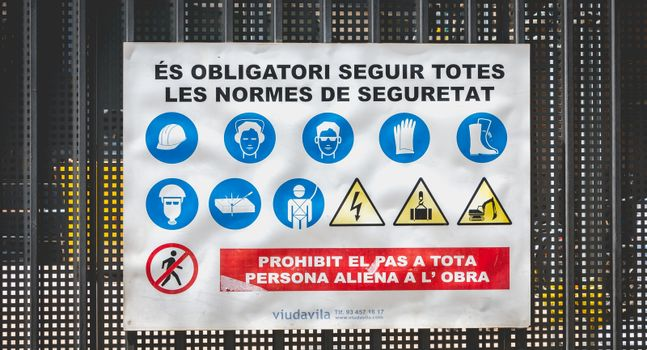Barcelona, Spain - June 21, 2017: at the entrance to a construction site, sign written in Catalan - it is mandatory to comply with all safety rules (es obligatori seguir totes les standards de seguretat)