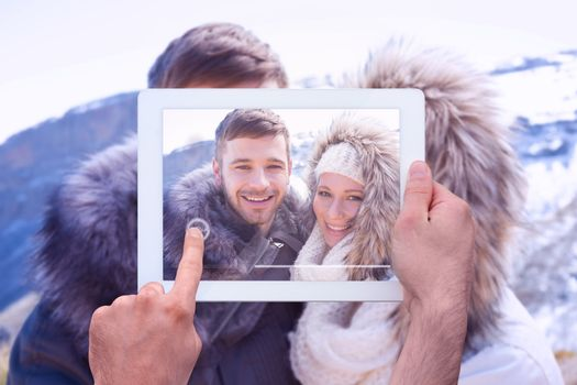 Hand holding tablet pc against loving couple in jackets against snowed mountain