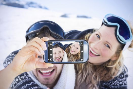Hand holding smartphone showing against cheerful couple with ski goggles on snow