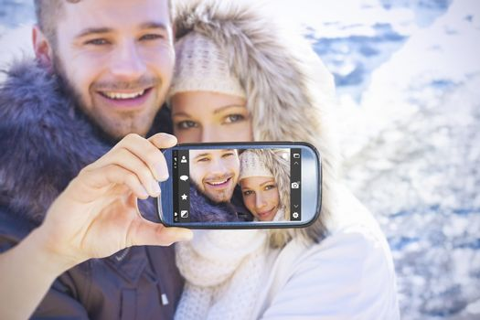 Hand holding smartphone showing against couple in jackets embracing against snowed mountain