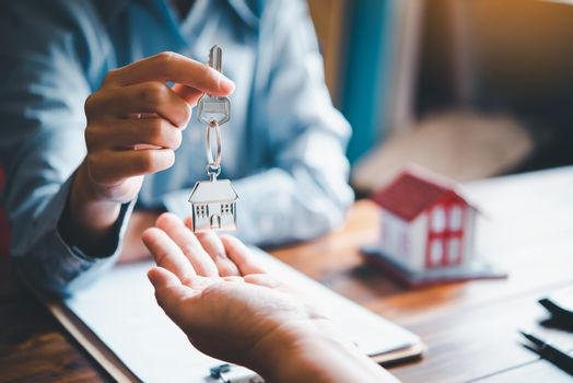 real estate agent gives the keys to the house buyer and signs th