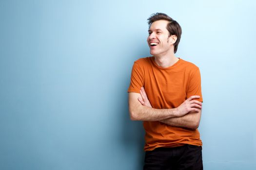 Candid carefree laughing man standing by wall