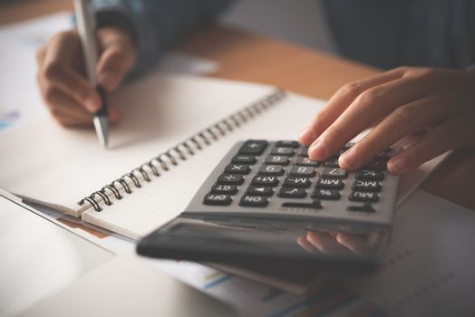 The accountant's hand is using the calculator. For cost analysis
