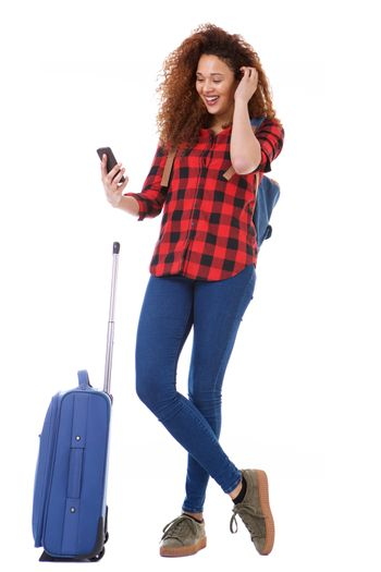 Full body female traveler with bags looking at cellphone