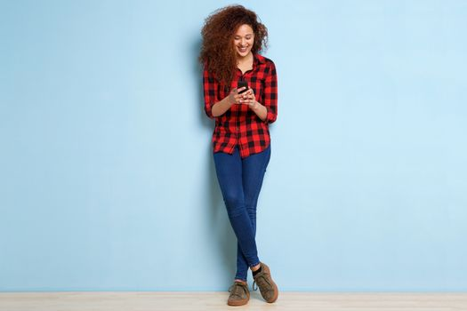 Full body happy young woman looking at mobile phone