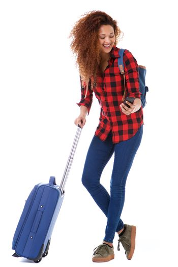 Full body happy woman with luggage looking at mobile phone