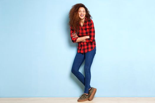 Full body happy young woman leaning against blue wall