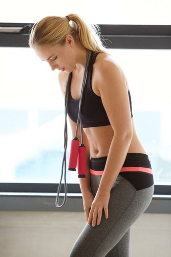 portrait of young blond woman standing with jump rope