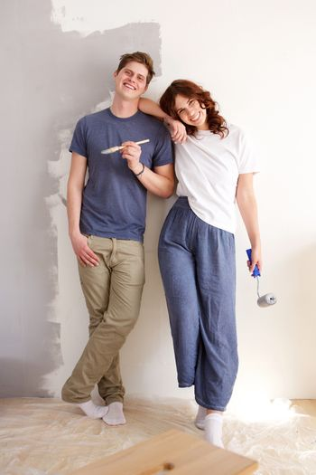Full body happy couple standing by wall with paint brushes