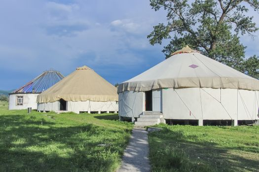 A row of traditional constructed yurts in Kalajun Grassland, Xinjiang, China. Uncompleted rooftop in the last yurt