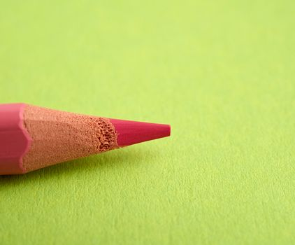 sharpened pink pencil on a green background