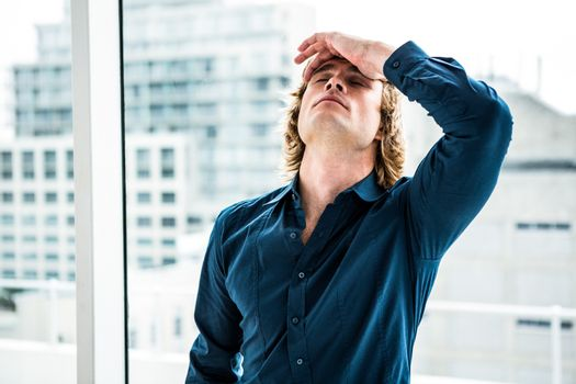 Troubled hipster businessman holding his head