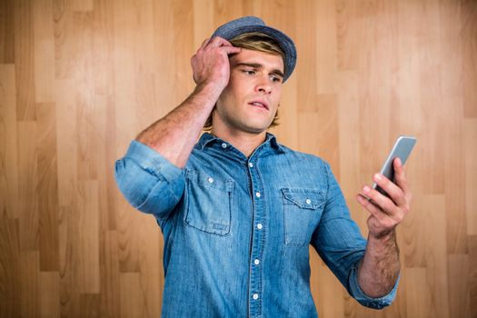 Concerned hipster looking at smartphone