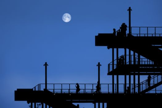 a passage of steel with people by night with moon