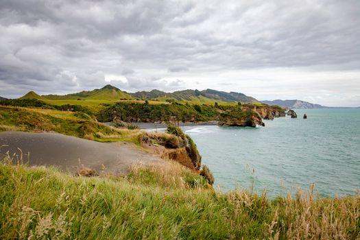 An image of sea shore rocks and mount Taranaki, New Zealand