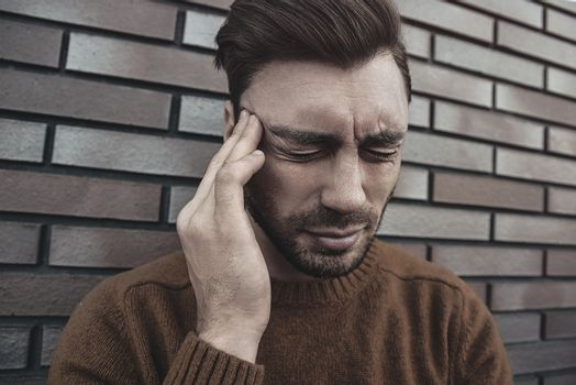 Man feeling painful emotions, screaming, witnessing death of close friend, being miserable and devastated, holding palms on head, yelling from pain and stress, standing unhappy over brown brick wall.