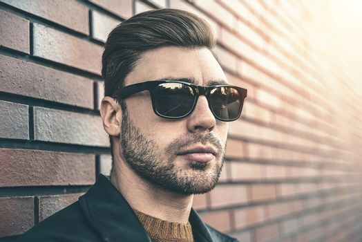 Portrait of stylish handsome young man with bristle standing outdoors and leaning on brick wall. Man wearing jacket, sweater and sunglasses.