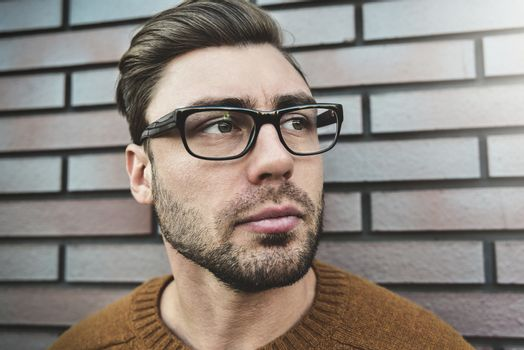 Portrait of a caucasian handsome man in eyeglasses that is seriously frowning. Emotional face concept.