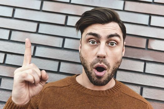 Great idea! Handsome man keeping finger pointed upwards, showing something above his head, making gesture with index finger. Eureka, solution sign concept.