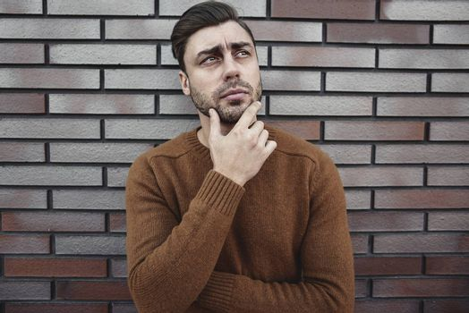Portrait of handsome serious man thinking about something isolated on brown brick wall.
