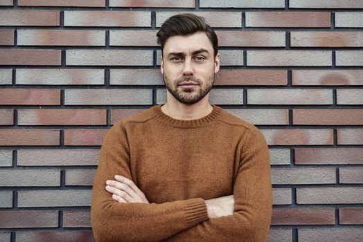 Portrait of serious manly stunning man in sweater looking at camera standing on street.