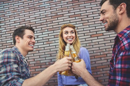 The three happy friends enjoying with beer on a brown brick wall background.