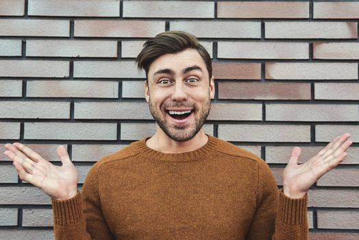 Portrait of cheerful man in urban city brick wall background lifestyle portrait. Career and entrepreneurship concept.