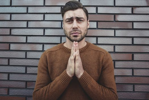 Young adult man standing over white brick wall begging and praying with hands together with hope expression on face very emotional and worried.