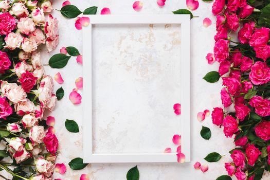 Various brightly colored pink and red roses directed at each other on rustic white and gold surface and empty white wooden frame.  Top view, blank space
