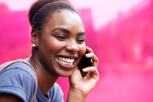 candid portrait of happy young african woman talking on cellphone