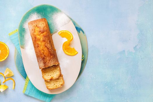 Glazed orange pound cake partly sliced and fresh citrus fruits.Top view, blank space